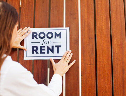 """woman posting """"room for rent"""" sign on wooden fence"""