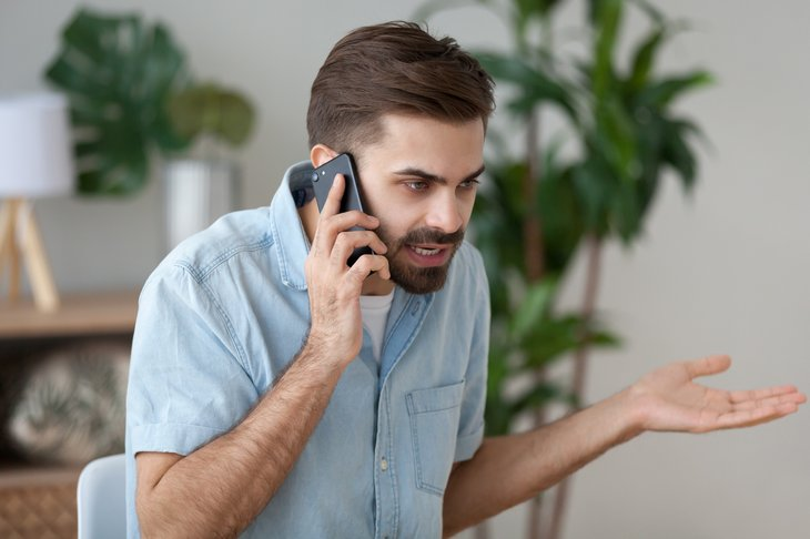 An annoyed man argues on the phone