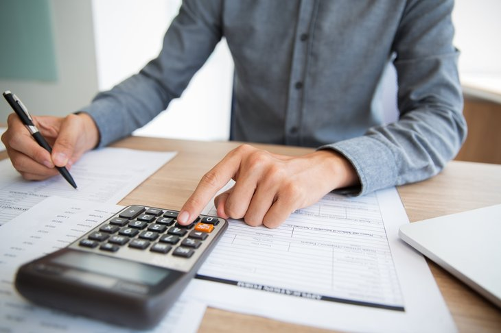 Person at desk with papers, calculator