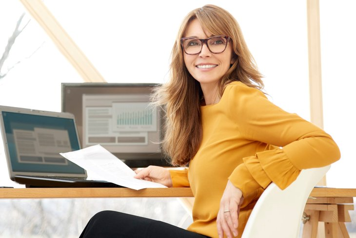 A successful high-earning businesswoman works at her desk