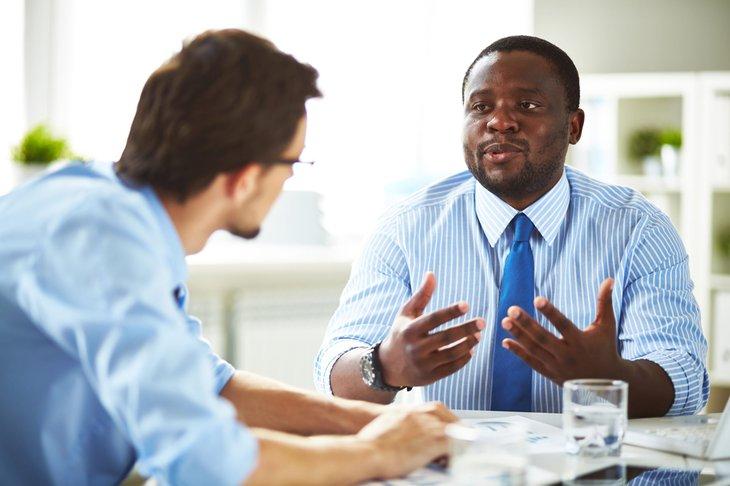 2 men black white business lawyers work talking