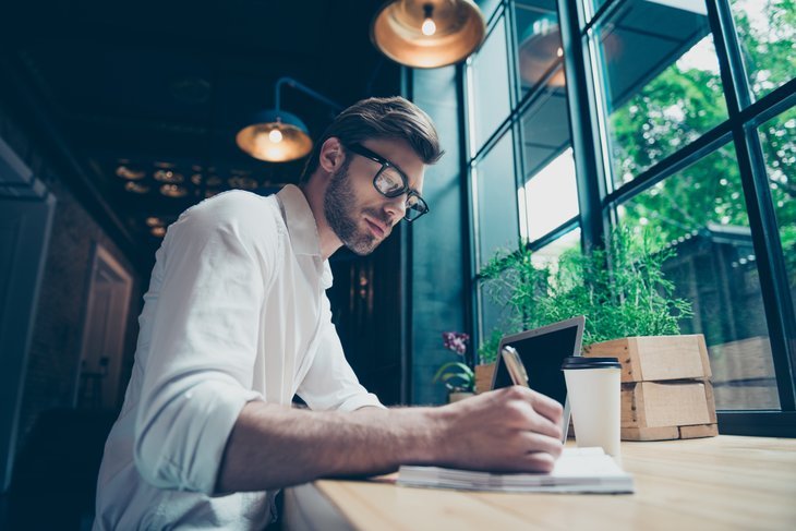 Man sitting at table writing.