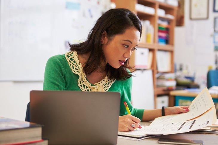 Asian woman teacher checking homework at her desk.